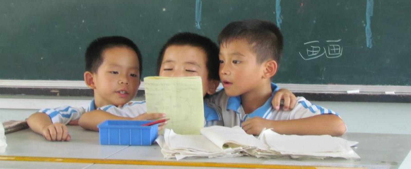 A Projects Abroad volunteer working with children in China listens to young boys reading aloud to improve their reading skills.